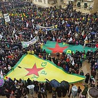 This photo released by the press office of the Kurdish militia, People's Protection Units or YPG, shows protesters waving giant flags of the YPG and other parties and militias, during a demonstration against Turkish threats, in Afrin, Aleppo province, north Syria on Thursday, Jan 18, 2018. (YPG Press Office via AP)
