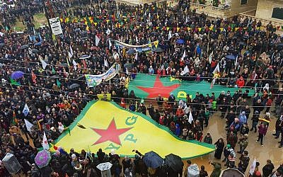 This photo released by the press office of the Kurdish People's Protection Units, or YPG, shows protesters waving giant flags of the YPG and other parties and militias, during a demonstration against Turkish threats, in Afrin, Aleppo province, Syria, on January 18, 2018. (YPG Press Office via AP)