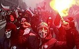 In this file photo from November 11, 2016, far-right nationalists burn flares as they march in large numbers through the streets of Warsaw to mark Poland's Independence Day. (AP Photo/Czarek Sokolowski, File)