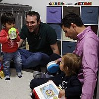 Elad Dvash-Banks, right, and his partner, Andrew, play with their twin sons, Ethan, left, and Aiden in their apartment Tuesday, Jan. 23, 2018, in Los Angeles. (AP Photo/Jae C. Hong)