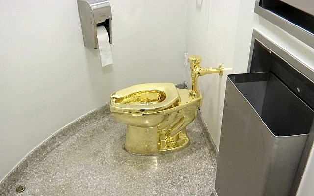"""An 18-karat toilet, titled """"America,"""" by Maurizio Cattelan in the restroom of the Solomon R. Guggenheim Museum in New York (screenshot)"""
