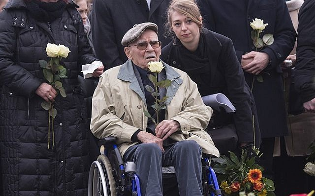 Former Nazi concentration camp survivor Raymond Renaud of France holds a white rose during the wreath-layin  ceremony on occasion of International Holocaust Remembrance Day in the former Nazi concentration camp Buchenwald near Weimar, Germany, Friday, Jan. 26, 2018. (AP Photo/Jens Meyer)