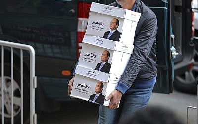 "In this undated file image released Wednesday, Jan. 24, 2018 on the official Facebook account of Egyptian President Abdel-Fattah el-Sissi, shows workers carrying boxes that bear the president's image and the phrase ""long live Egypt!"" in Cairo, Egypt. (Egyptian President's Facebook page via AP, File)"