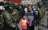 In this Jan. 24, 2018 file photo, people walk by special forces soldiers guard in front of the National Election Authority, which is in charge of supervising the 2018 presidential election, in Cairo, Egypt. (AP Photo/Amr Nabil, File)