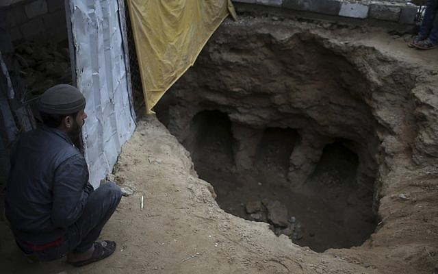 A Palestinian man looks at a discovered tomb consisting of nine burial holes, which was found by Abdelkarim al-Kafarna, in his backyard in Beit Hanoun, northern Gaza City, Friday, January 26, 2018. (AP Photo/ Khalil Hamra)