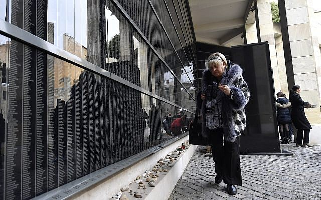 Illustrative: Hungarian Holocaust survivor, Katalin Sommer, lights a candle at the Victims' Memorial Wall bearing names of victims during a commemoration marking the International Holocaust Remembrance Day in the Holocaust Memorial Center in Budapest, Hungary, Friday, January 26, 2018, (Tibor Illyes/MTI via AP)