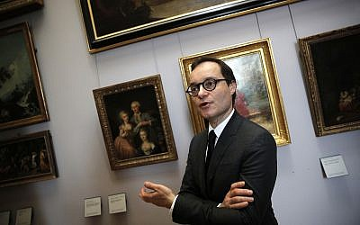 Head of the paintings department at the Louvre museum, Sebastien Allard, poses next to paintings looted by Nazis during World War II, at the Louvre museum, in Paris, Tuesday, Jan. 30, 2018. (AP Photo/Christophe Ena)