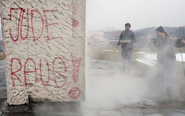 Illustrative photo: Workers removing anti-Semitic graffiti from a Holocaust memorial at a former Nazi concentration camp in Plaszow, southern Poland, on Saturday, March 13, 2010. (AP)