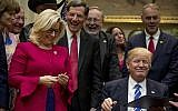 President Donald Trump gives his pen to Republican Congresswoman Liz Cheney, third from left, after signing one of various bills in the Roosevelt Room of the White House in Washington, Monday, March 27, 2017. (AP Photo/Andrew Harnik)