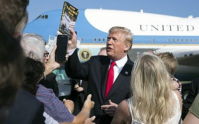 Illustrative image of US President Donald Trump holding up the book 'How Trump Won The Inside Story of a Revolution' on the tarmac  at Palm Beach International Airport, December 22, 2017. (AP Photo/Carolyn Kaster)