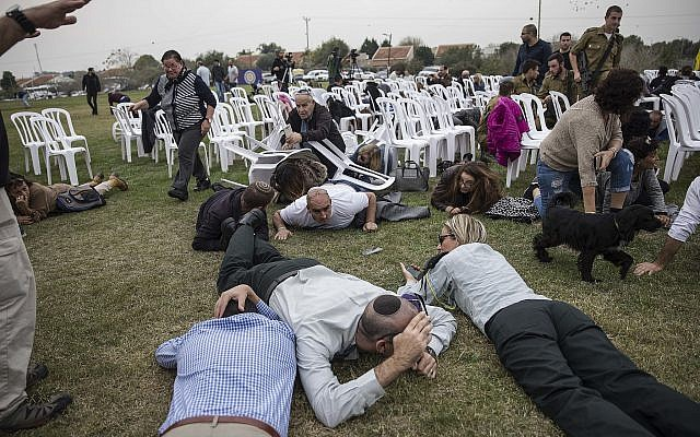 Illustrative: Israelis take cover during rocket attack siren warning in kibbutz Kfar Aza near the Israel and Gaza border, Israel, December 29, 2017. (AP/Tsafrir Abayov)