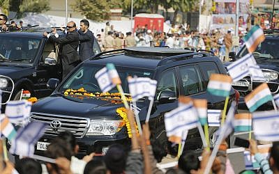 Indian children wave to a vehicle carrying Israeli Prime Minister Benjamin Netanyahu and Indian Prime Minister Narendra Modi as they arrive at Sabarmati Ashram or Gandhi Ashram in Ahmadabad, India, Wednesday, Jan. 17, 2018. (AP/Ajit Solanki)