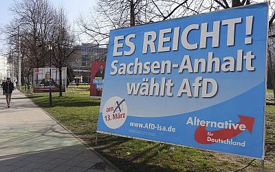 In this Wednesday, March 9, 2016 photo a man walks past a campaign poster of right-populist AfD party reading 'It's enough - Saxony-Anhalt elects AfD' in Magdeburg, Germany (AP Photo/Geir Moulson)
