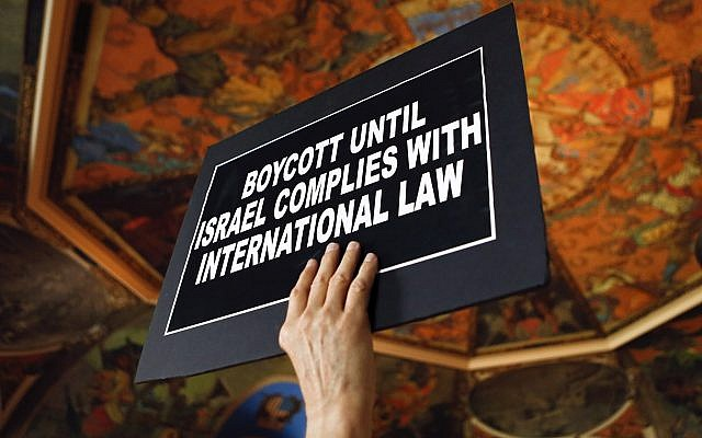 A man holds a sign during a rally in support of the BDS movement in Albany New York, on June 15, 2016. (AP/Mike Groll)