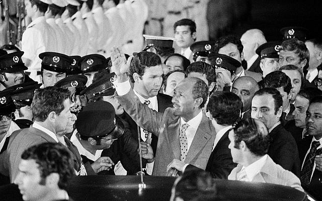 Egyptian president Anwar Sadat is surrounded by security people as he waves to cheering crowds on his arrival in Israel, Nov. 19, 1977. (AP Photo)