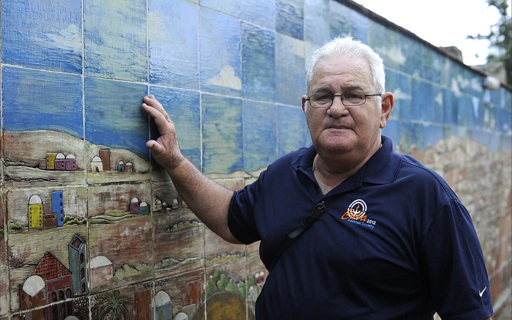 David Tacher, president of Santa Clara's Jewish community, stands next to a recently completed mural of Jerusalem in the synagogue's courtyard. (Larry Luxner/Times of Israel)