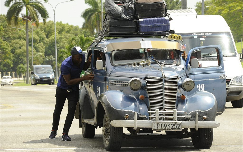 A taxi driver has no choice but to push his loaded taxi. (Larry Luxner/Times of Israel)