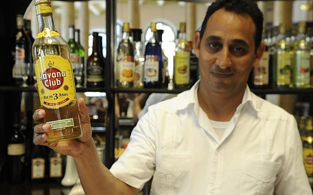 Illustrative: Wilbert Wilson Rivero, a Jewish bartender who works at Havana's Hotel Raquel, proudly displays a bottle of Havana Club rum. (Larry Luxner/Times of Israel)