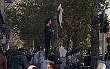 "Iranian woman waving a white scarf -- an apparent reference to so-called ""White Wednesday"" protests against mandatory clothing rules for women, December 27. (Screen capture: YouTube)"