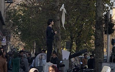 An Iranian woman waving a white scarf -- an apparent reference to so-called 'White Wednesday' protests against mandatory clothing rules for women, December 27, 2017, in Tehran, Iran. (Screencapture: YouTube)