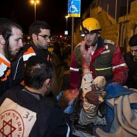 Rescue and medic personnel, including ultra-Orthodox paramedics, carrying a wounded woman at the scene of where the top floor of a building collapsed after a gas tank exploded in the Gilo neighborhood, Jerusalem, January 20, 2014. (Yonatan Sindel/Flash90)