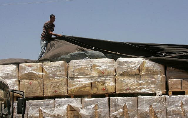 A Palestinian checks a truck loaded with humanitarian aid from the US as it arrives in the Palestinian town of Rafah through the Kerem Shalom crossing between Israel and the southern Gaza Strip on August 6, 2014.