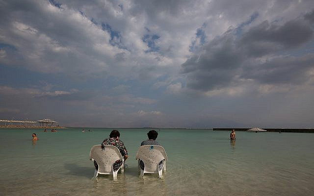 People sit by the water at Hamei Zohar beach at the Dead Sea, November 10, 2015. (Nati Shohat/Flash90)