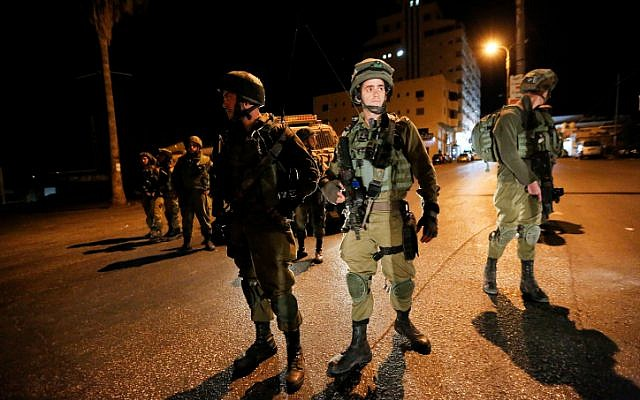 Illustrative. Israeli soldiers seen during a raid on the al-Huriya radio station on suspicion of incitement to violence in the West Bank city of Hebron on August 31, 2017. (Wisam Hashlamoun/Flash90)