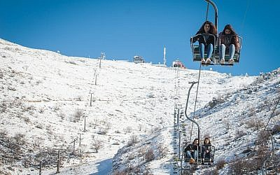 People enjoy the snow at Mount Hermon ski resort, in northern Israel, on December 25, 2017. (Basel Awidat/Flash90)