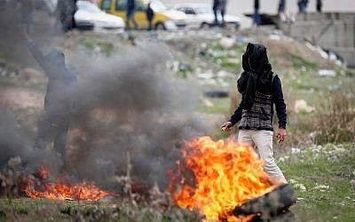 Palestinians clash with Israeli soldiers during clashes in Al-Fawwar refugee camp, south of the West Bank city of Hebron, on December 31, 2017. (Wisam Hashlamoun/Flash90)