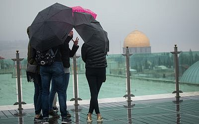 File: Tourists look out over Jerusalem's Old City, as seen from the rooftop of the Austrian hospice, on a foggy winter day, January 2, 2018. (Miriam Alster/Flash90)