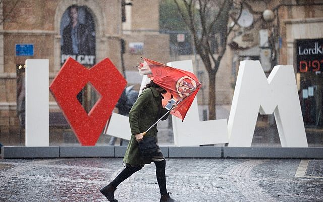People hold umbrellas to protect themselves from the rain as they walk in Jaffa street in Jerusalem, as heavy rain and wind storm hits Israel. January 05, 2018. (Yonatan Sindel/Flash90)