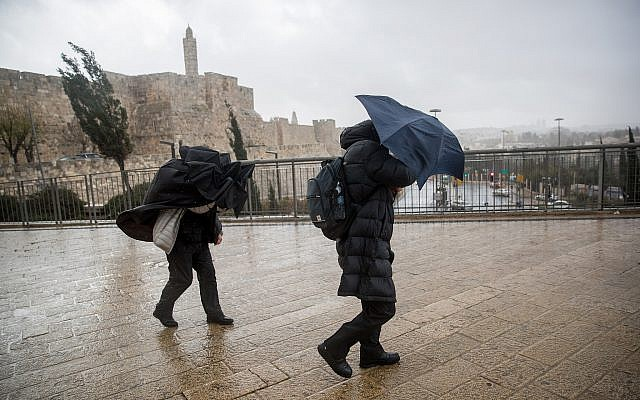 People hold umbrellas to protect themselves from the rain as they walk in Jaffa gate near the Tower of David in Jerusalem Old City, as heavy rain and wind storm hits Israel. January 05, 2018. (Yonatan Sindel/Flash90)