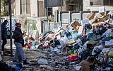 Shoppers walk past piles of garbage left by striking city workers, at Jerusalem's Mahane Yehuda Market, on January 7, 2018. (Yonatan Sindel/Flash90)