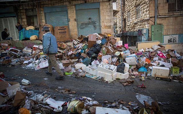 Shoppers walk past piles of garbage left by striking city workers, at Jerusalem's Mahane Yehuda Market, on January 7, 2018. (Yonatan Sindel/Flash90)
