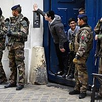 Children look out from a doorway as armed soldiers patrol outside a school in the Jewish quarter of the Marais district in Paris, January 13, 2015. (Jeff J. Mitchell/Getty Images)