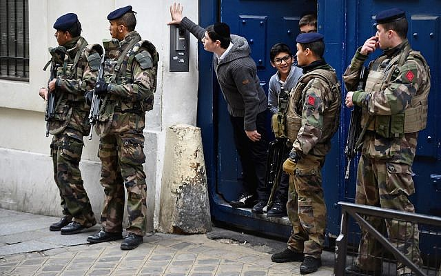 Illustrative: Children look out from a doorway as armed soldiers patrol outside a school in the Jewish quarter of the Marais district in Paris, January 13, 2015. (Jeff J. Mitchell/Getty Images)