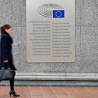 A woman walks past a placard with the words European Parliament inscribed in several languages of the European Union member states outside the Espace Leopold on February 25, 2016 in Brussels, Belgium. (Ben Pruchnie/Getty Images via JTA)
