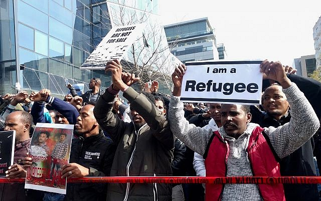 "Eritrean demonstrators chanted ""Refugees, not infiltrators,"" outside of the Rwandan Embassy in Herzilya on January 22, 2018. (Melanie Lidman/ Times of Israel)"