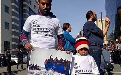 A father and son protest the planned deportations outside of the Rwandan Embassy on January 22, 2018. (Melanie Lidman/Times of Israel)