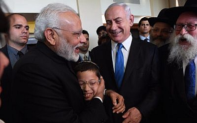 Indian Prime Minister, left, embracing 11-year-old Moshe Holtzberg, whose Chabad emissary parents were killed in a 2008 terror attack in Mumbai, with Prime Minister Benjamin Netanyahu on left in Israel, July 5, 2017 . (Haim Zach/Israeli Government Press Office)