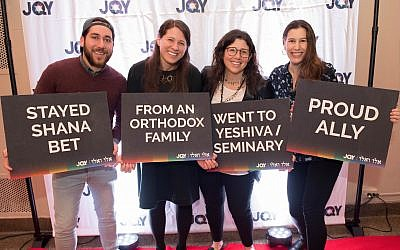 Participants hold signs at a concert held by Jewish Queer Youth. (Courtesy JQY)