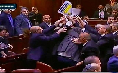 """Knesset ushers eject lawmakers from the Joint (Arab) List from the plenum after they hold up signs reading """"Jerusalem is the capital of Palestine"""" at the start of US Vice President Mike Pence's speech on January 22, 2018. (Screen capture/Twitter)"""