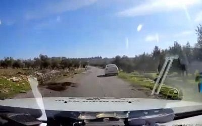 Still from video of police car rescuing tourist vehicle that strayed into West Bank Arab village of Teqoa on January 9, 2018. (Screen capture: Hadashot news)