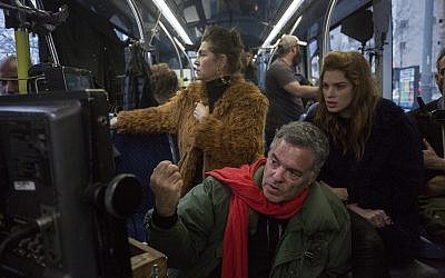 Amos Gitai (bottom) with Keren Mor (left) and Yuval Sherf, checking takes during filming of 'Jerusalem Light Rail.' (Courtesy Amos Gitai)