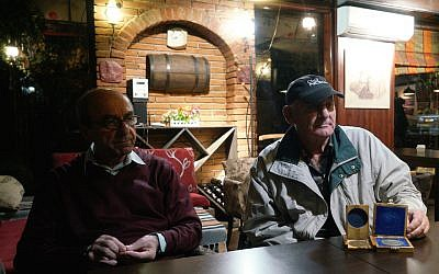 Rexhep Hoxha, left, and Fatos Qoqja in a bar in Tirania, Albania, November 8, 2017. Qoqja is pictured with a medal that his father received for saving Jews during the Holocaust. (Cnaan Liphshiz/via JTA)