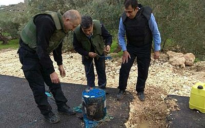 Palestinian Authority security forces inspect a roadside bomb found in the West Bank on Saturday, January 27, 2018. (Ma'an news agency)