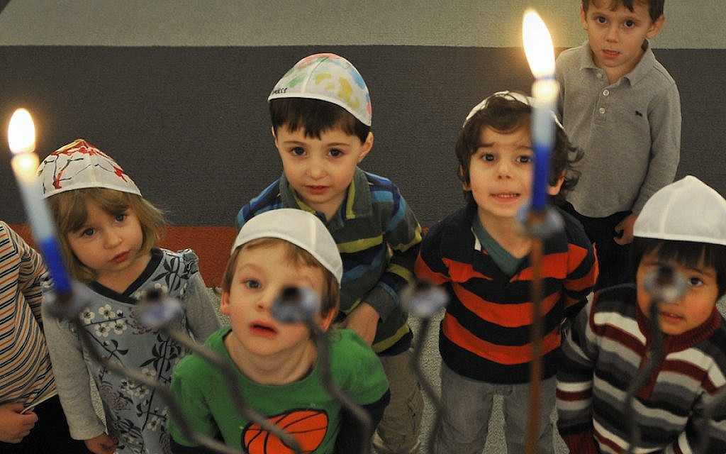 Jewish preschoolers in Washington, DC, gaze at a Hanukkah menorah. (Mark Gail/The Washington Post via Getty Images/JTA)
