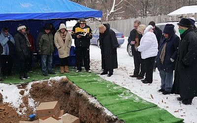 Congregants from Temple Hadar Israel in New Castle, Pennsylvania, gathering at the local Tifereth Israel cemetery to bury ritual objects from their defunct synagogue, December 31, 2017. (Alanna E. Cooper/JTA)