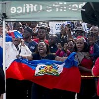 Haitians line the sidewalks as President Donald Trump's motorcade returns to Mar-a-Lago in West Palm Beach, Florida, on January 15, 2018. (AP Photo/Andrew Harnik)